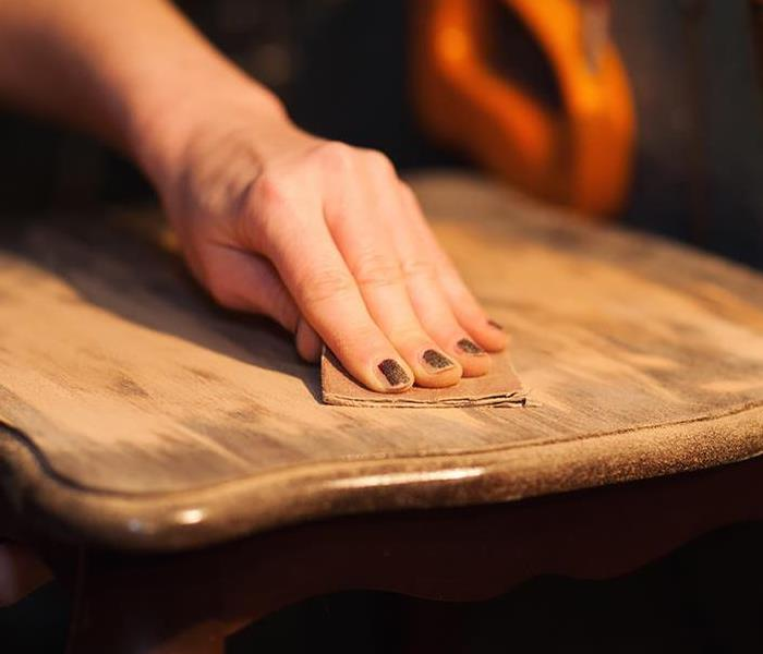 Feminine hand with painted nails resurfacing a wooden tabletop.